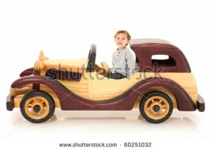 three year old-boy-sitting-in-wooden-toy-car-over-white-background-with-60251032
